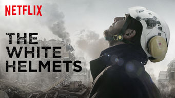 Photo of a White Helmet looking up to the sky, while the city behind him is in ruins